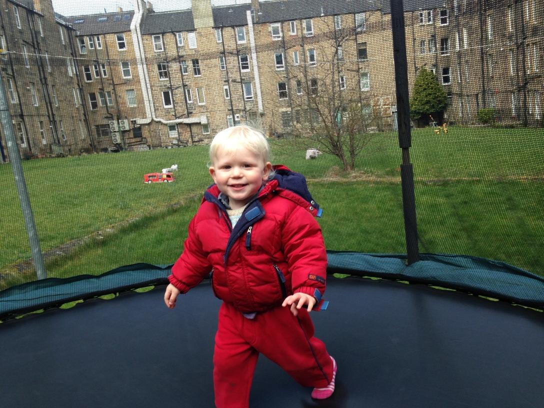 child on the trampoline in Edinburgh, red coat