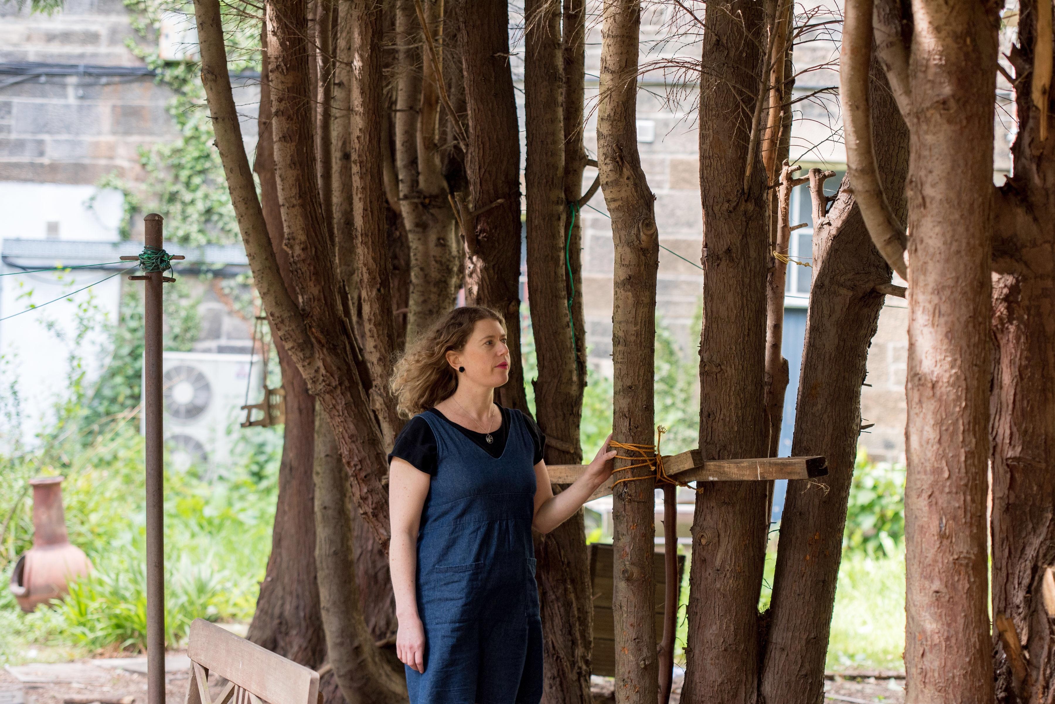 Woman stands in urban garden