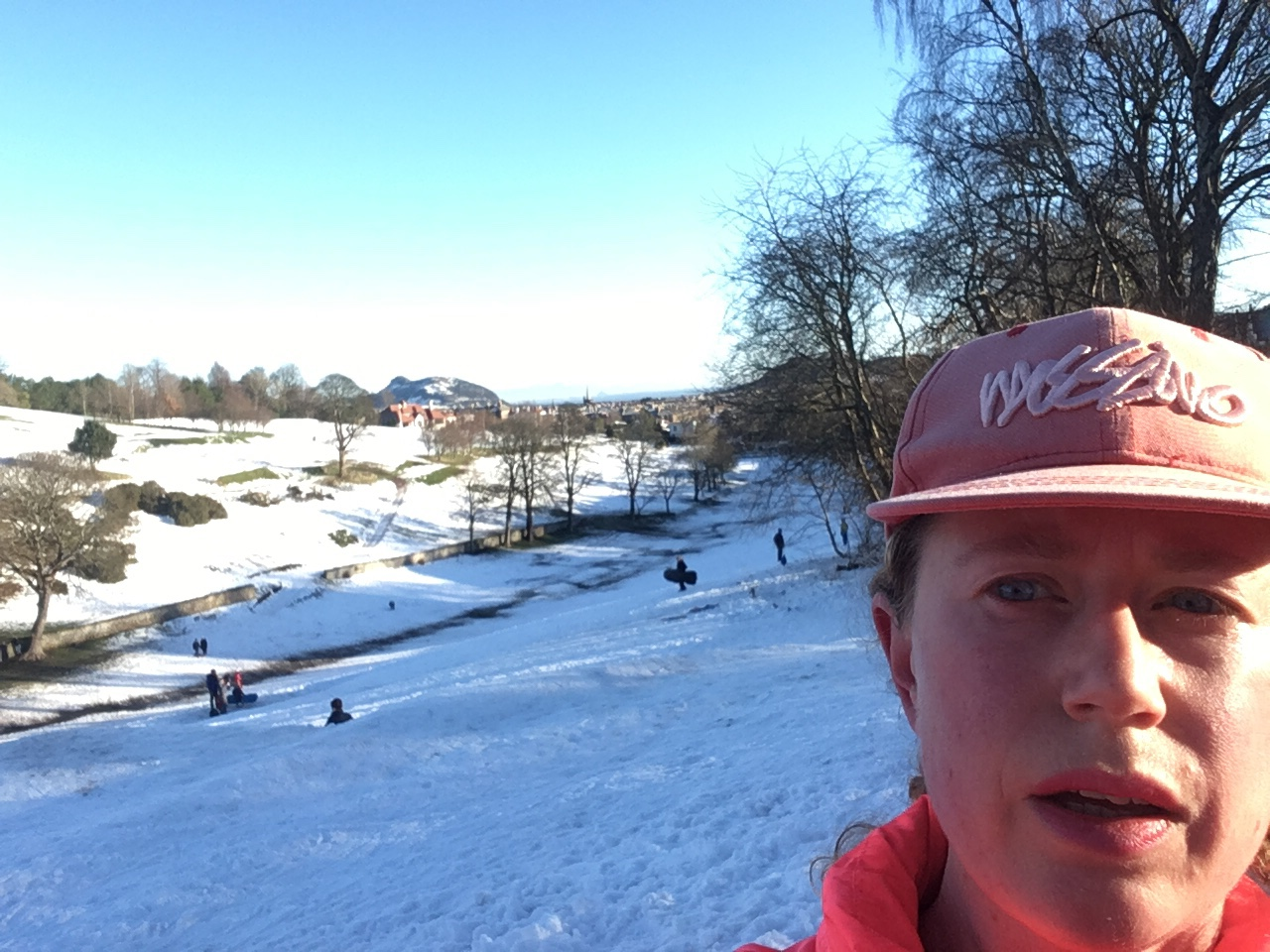 Woman in Run Selfie with snowy Edinburgh scene in the background.